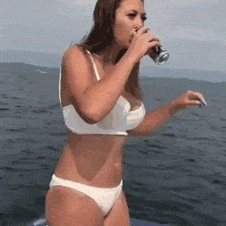 девушка пьет, стоя на яхте gif