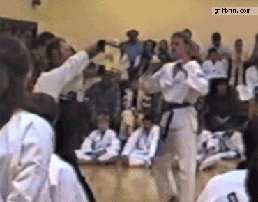 парень в кимоно бьет ногой по доске