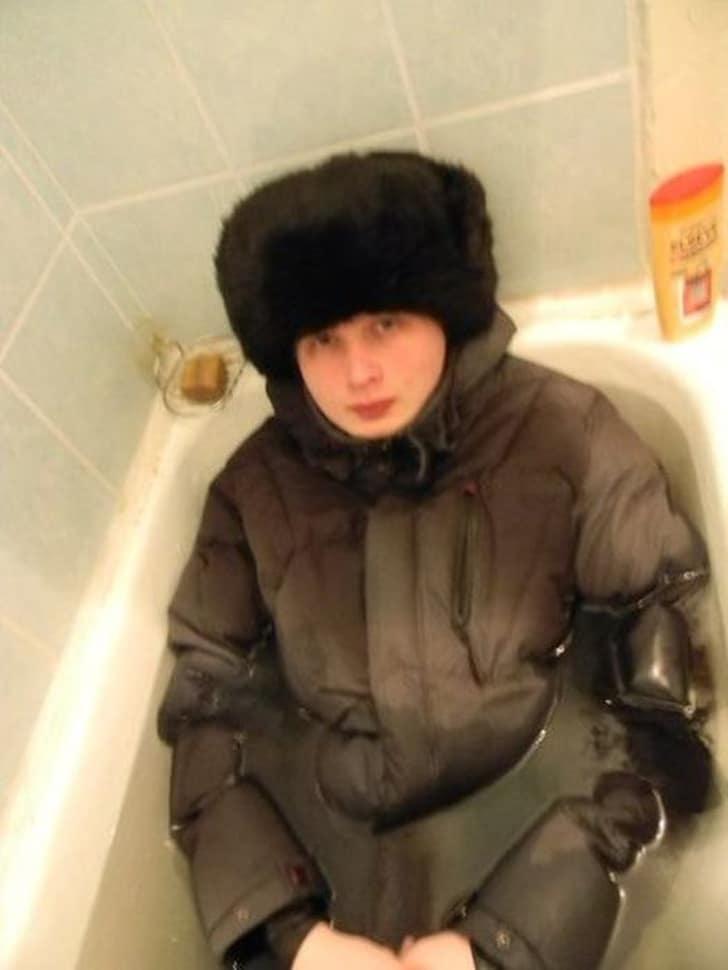 парень в куртке и шапке в ванне