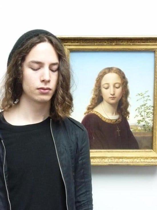 парень с длинными волосами на фоне портрета