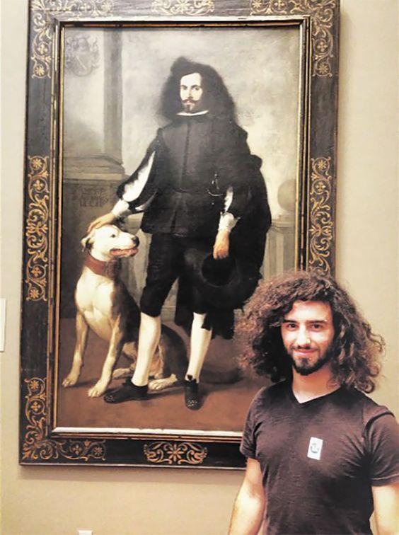 длинноволосый парень на фоне картины