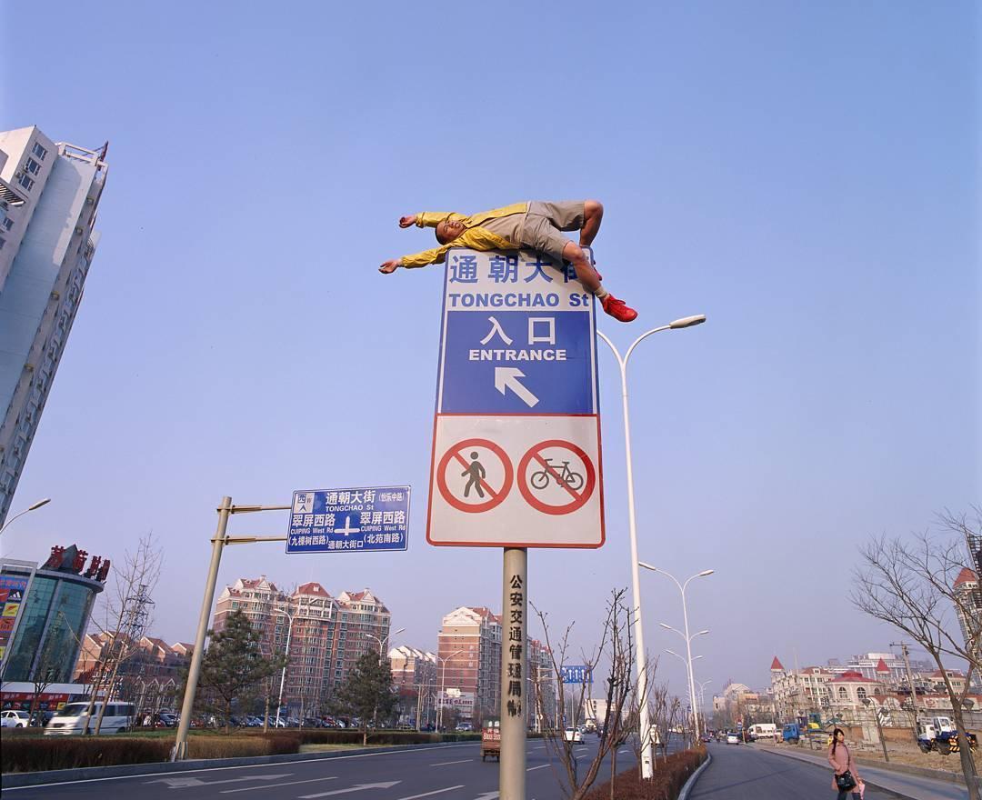 мужчина верхом на дорожном знаке