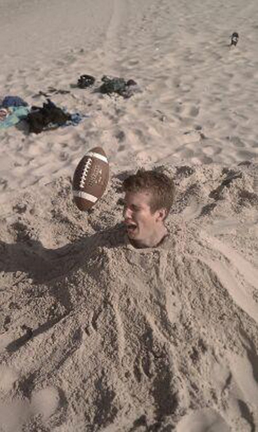 парень, зарытый в песок