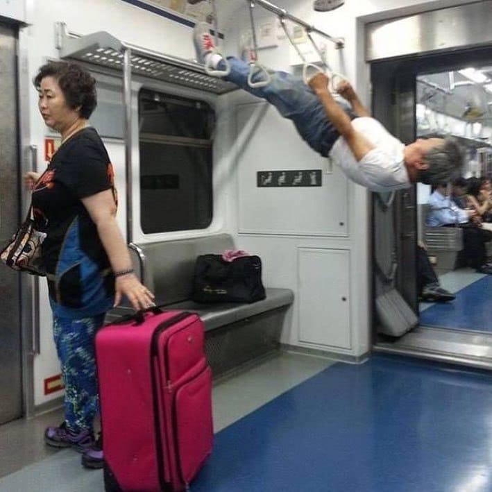 мужчина висит на поручнях в метро