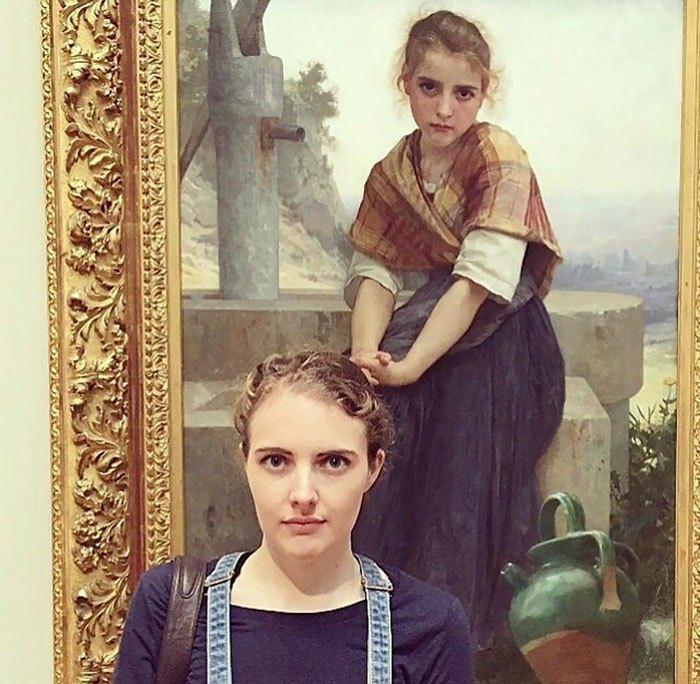девушка позирует на фоне портрета с двойником