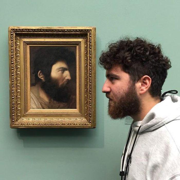 бородатый парень рядом с картиной