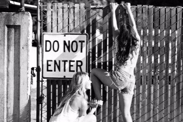 две девушки лезут на забор