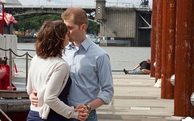пара целуется на фоне мужчины