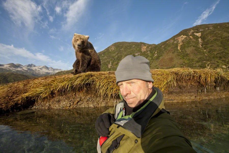 мужчина делает селфи на фоне медведя