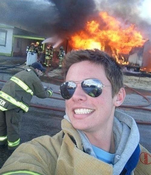 пожарный делает селфи на фоне пожара