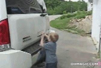 мальчик открывает багажник машины