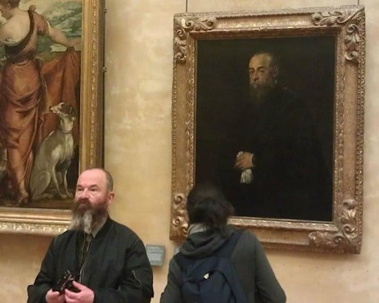 бородатый мужчина на фоне портрета