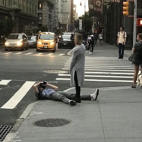 парень фотографирует девушку, лежа на асфальте