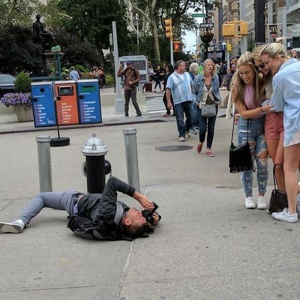 парень лежит на асфальте с фотоаппаратом