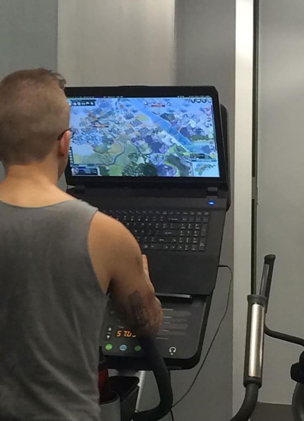 парень занимается на тренажере и играет в игры