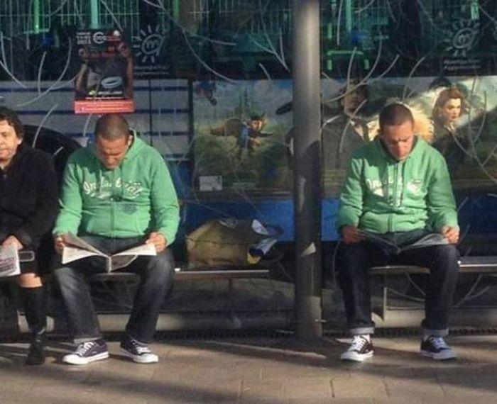 мужчины читают в парке на скамье