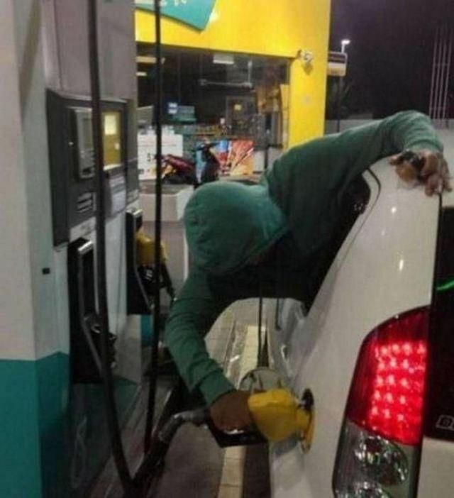 мужчина заправляет машину