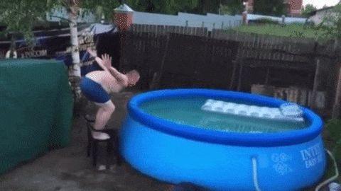 мужчина прыгает в бассейн