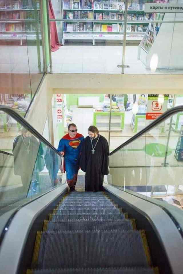 супергерой едет на эскалаторе с батюшкой