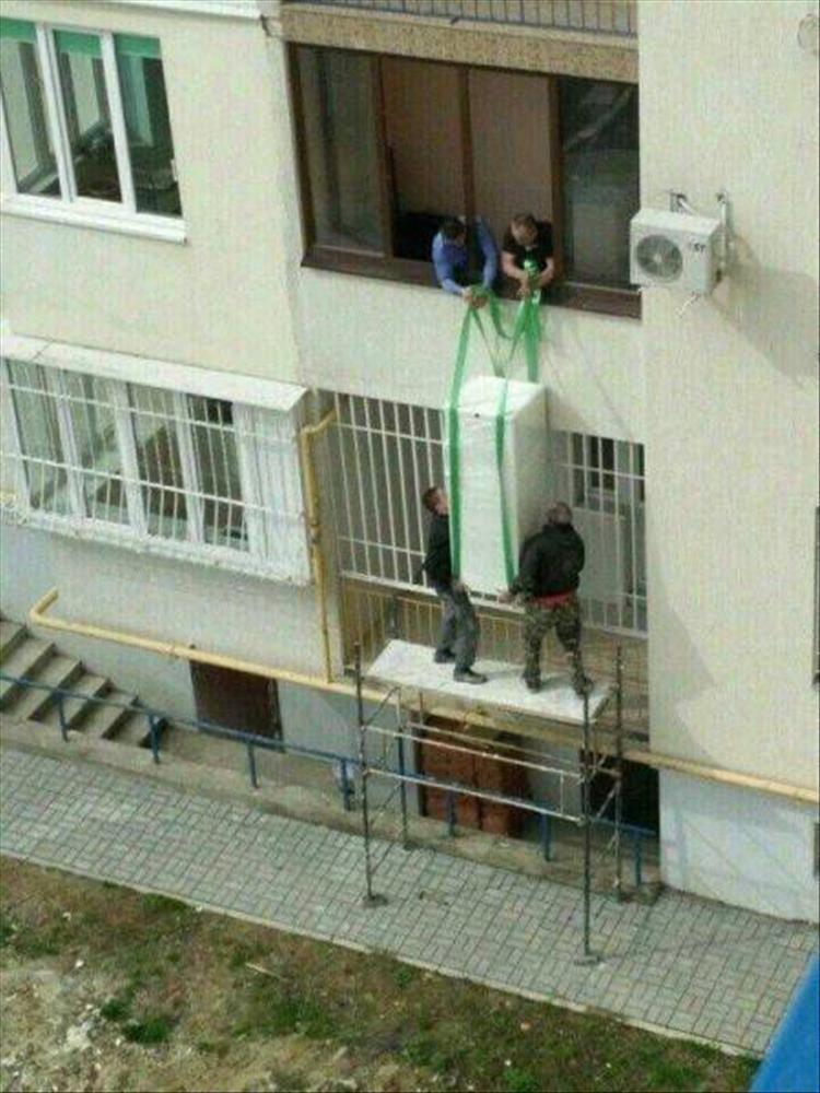 мужчины поднимают холодильник на балкон