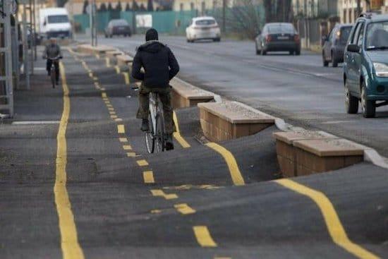 мужчина едет на велосипеде по кривой дороге
