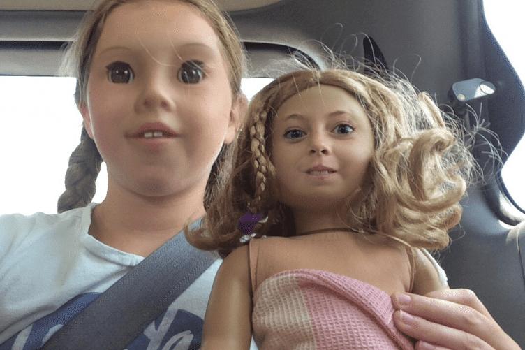 девочка с куклой в машине