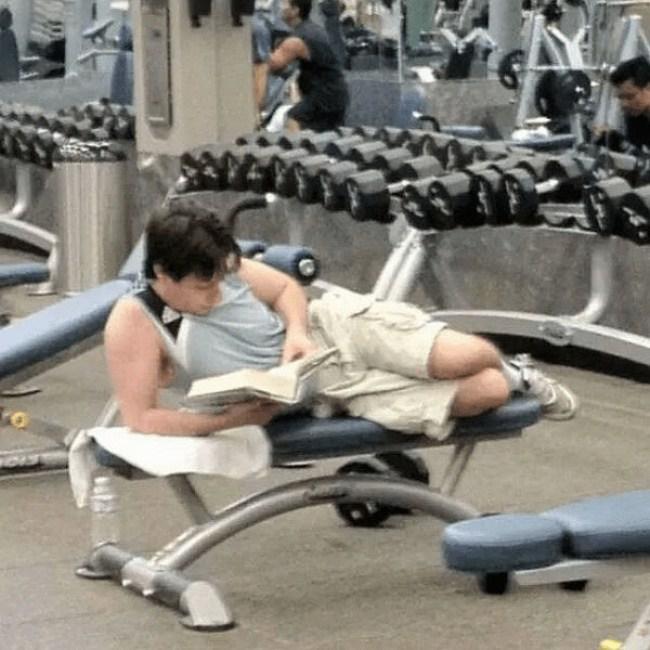 парень читает книгу в спортзале