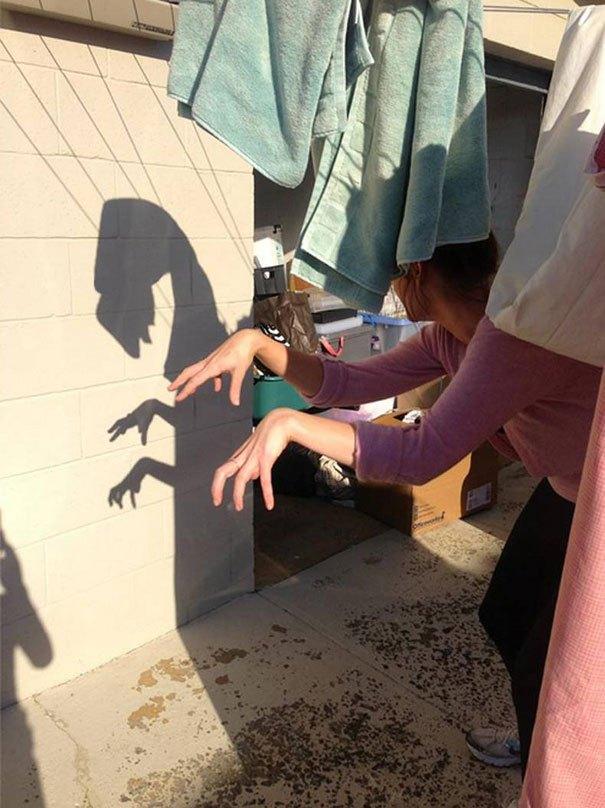 девушка играет с тенью на стене