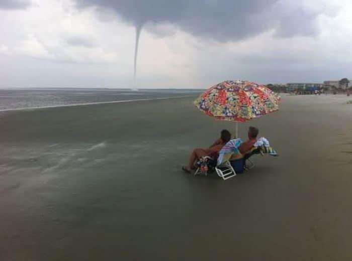 люди на пляже и ураган