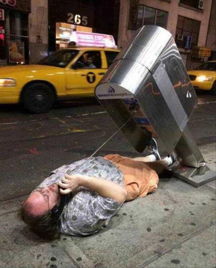 мужчина лежит на асфальте с телефонной трубкой в руке
