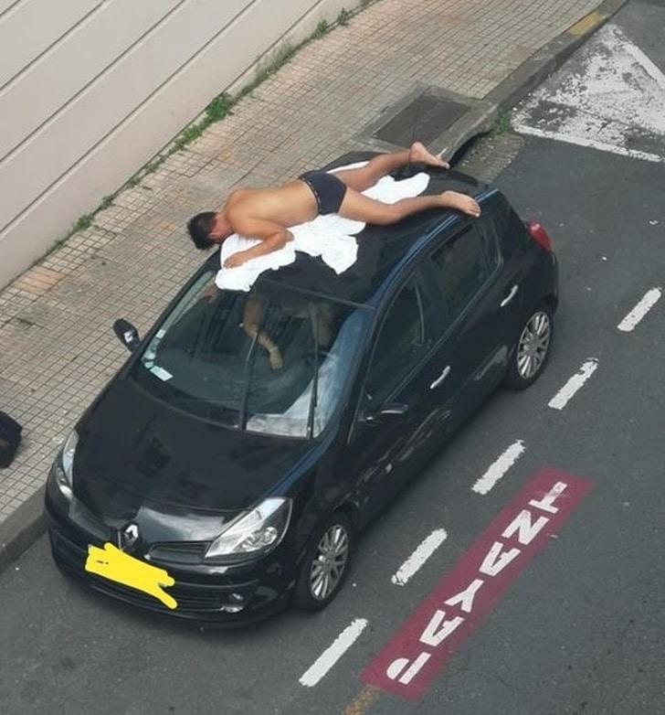 парень загорает на крыше автомобиля