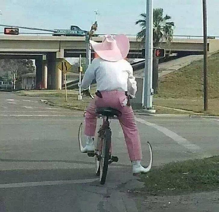 мужчина в розовой шляпе на велосипеде
