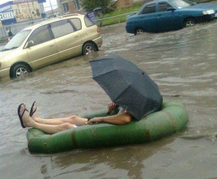 мужчина под зонтом на надувной лодке