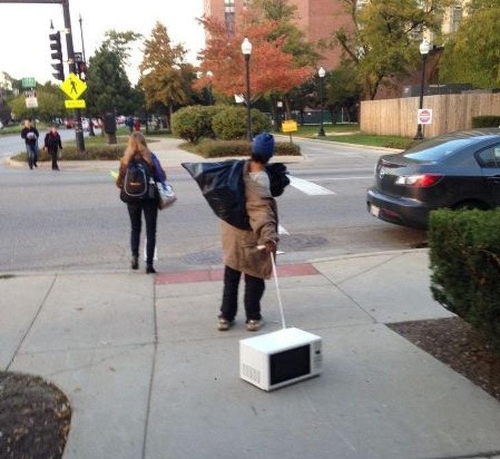 мужчина с микроволновкой на улице