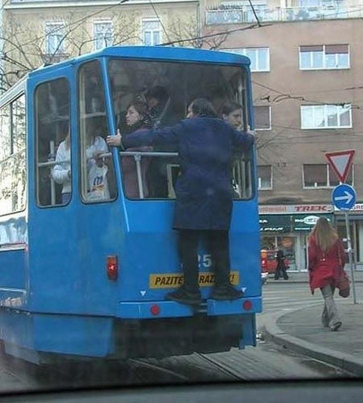 мужчина едет сзади на трамвае