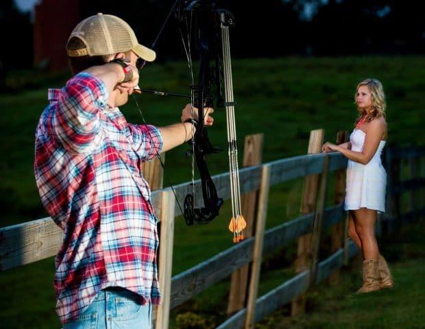 мужчина стреляет из лука в девушку