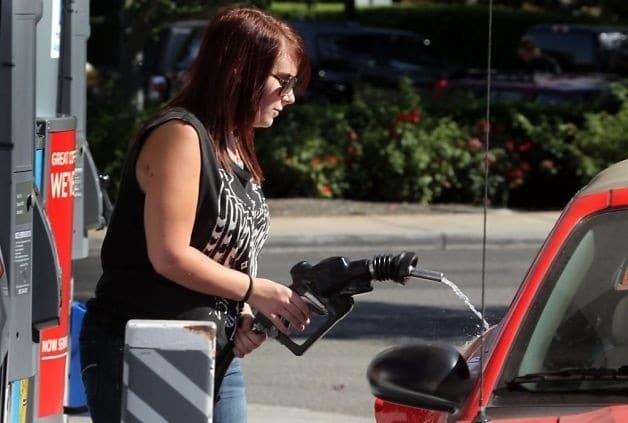 женщина заправляет машину