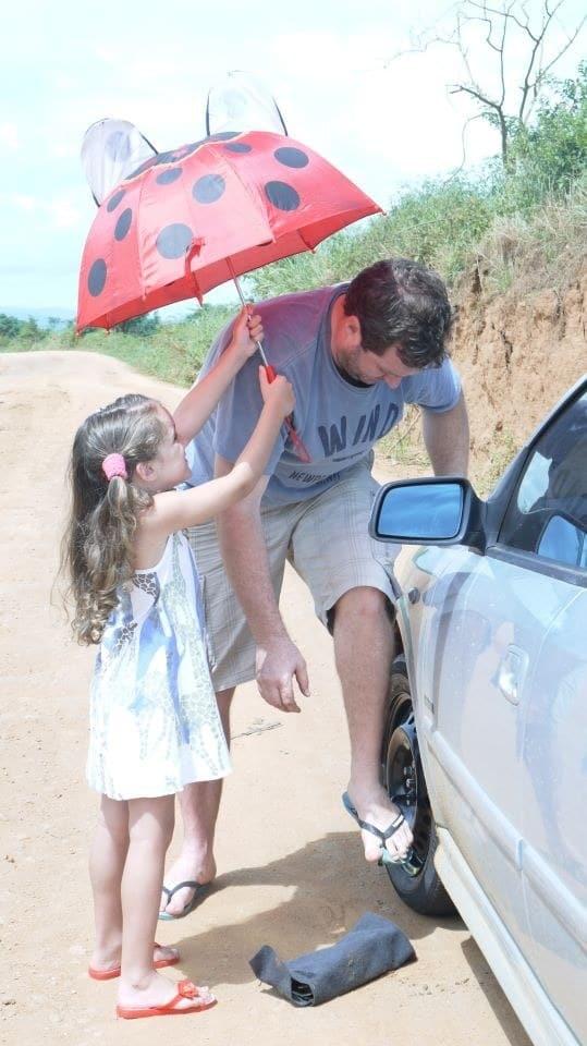 девочка держит зонт над папой