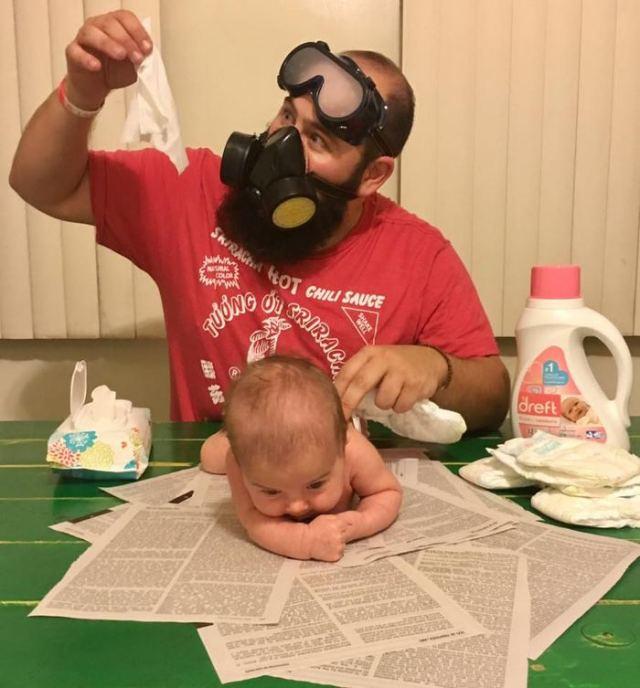 мужчина меняет ребенку подгузник