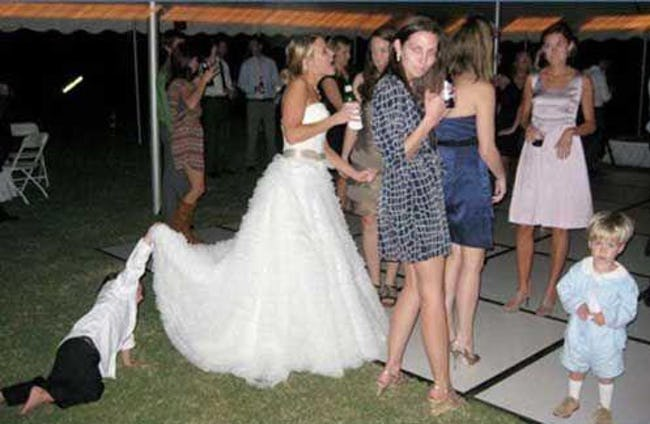 мальчик заглядывает под платье невесты