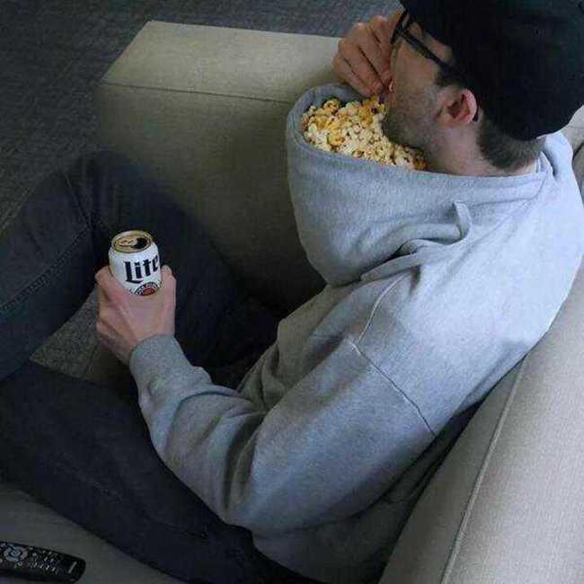 мужчина ест попкорн из капюшона