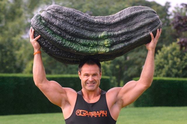 спортсмен держит очень большой кабачок