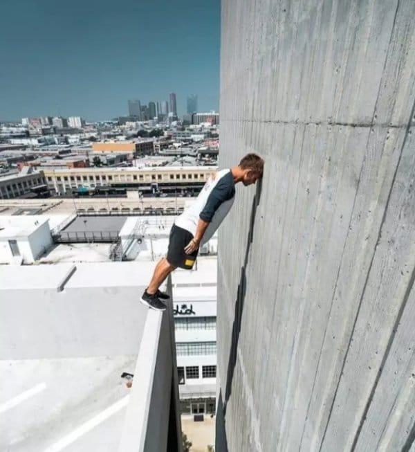 мужчина стоит на краю небоскреба