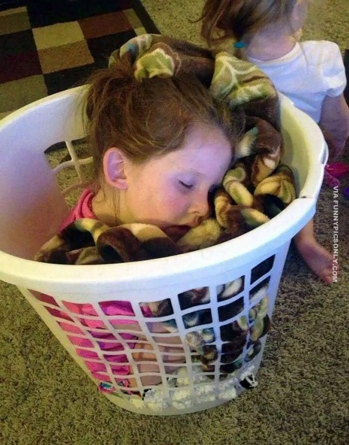 девочка спит в корзине для белья