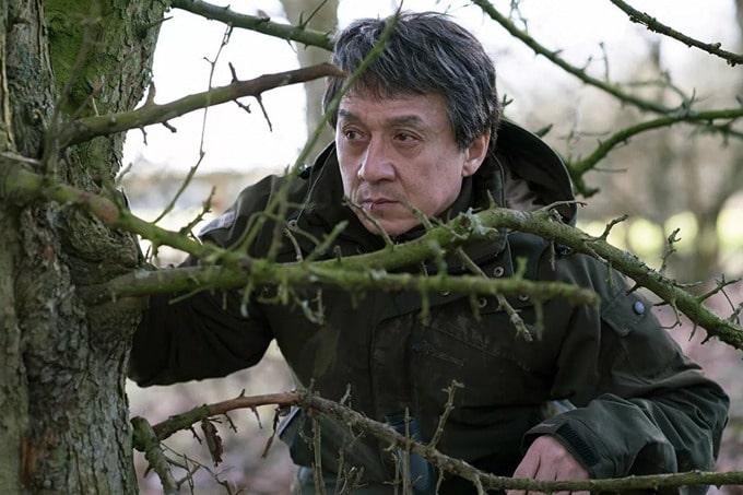 мужчина прячется в лесу за ветками