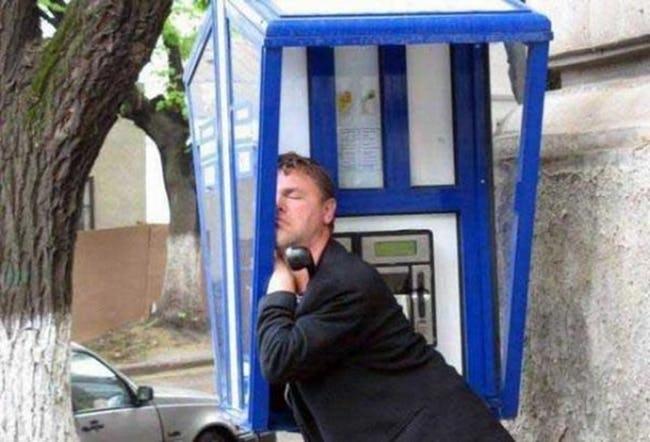 мужчина спит в телефонной будке