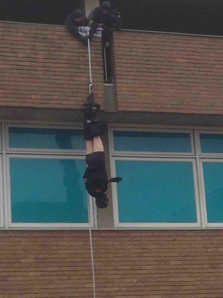 мужчина висит вниз головой за окном