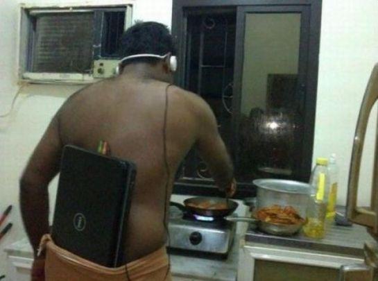 чернокожий мужчина с ноутбуком в кухне