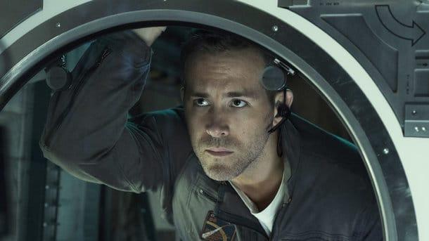 мужчина смотрит в иллюминатор космического корабля