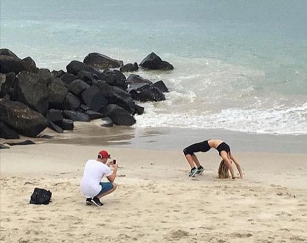 девушка делает мостик на пляже